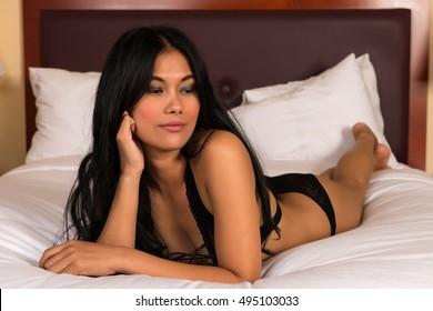 Beautiful petite Filipino woman in a black fishnet bodysuit