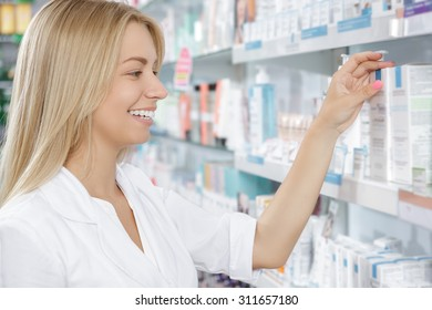 Beautiful pharmacist choosing the product in drugstore