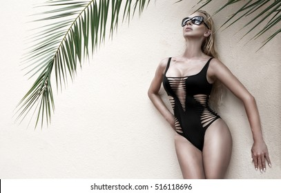 Beautiful phenomenal stunning elegant sexy blonde model woman with perfect face wearing a sunglasses stands with elegant erotic swimsuit on amazing view with palm tree shadow in Cannes, France