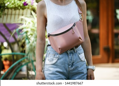 A beautiful phone bag on the shoulder of a sexy skinny girl in denim shorts. Close up.