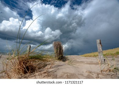 Beautiful photo along the Dutch coast strip with sand dunes on a sunny, windy storm day. Swaying dune grass and staggering sand dunes under an impressive cloudy sky