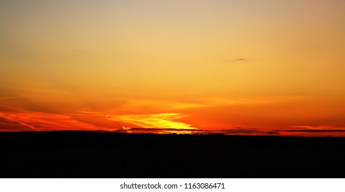 Beautiful photo of a bright sunset with clouds over a field in the summer evening
