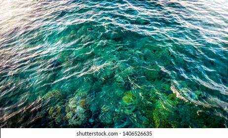 Beautiful photo of calm sea with clear turquoise water. Colorful corals and rocks on the sea bottom