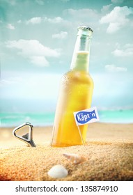 Beautiful photo of a chilled beer and a bottle opener on the beach tagged as Kapt'n.
