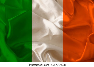 beautiful photo of the colored national flag of the modern state of Ireland on textured fabric, concept of tourism, emigration, economics and politics, closeup
