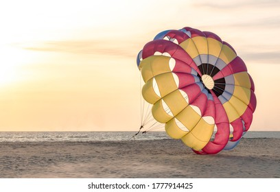 Beautiful photo of colorful parasailing parachute anchored on secluded beach for tourists loving adventure sports. Photo is well isolated. Concept of Growth, Independence, Resistance, lockdown etc.