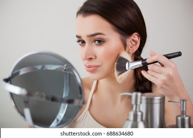 Beautiful Photo girl, woman in the mirror puts makeup brush for publication in magazine or advertisement