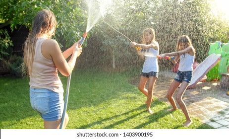 Beautiful photo of happy laughing family with children having fun at hot summer day with water guns and garden hose. Family playing and having fun outdoors at summer