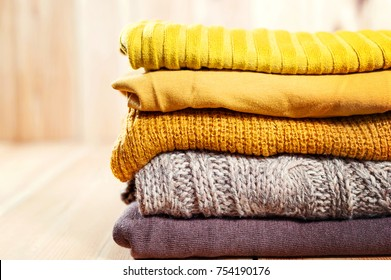Beautiful photo of a pile of knitted yellow woman sweaters. Woman fashion. Autumn clothing. Wonderful modern sweaters. Sewing industry. Stack of goods. Everything for your warmness. Retail