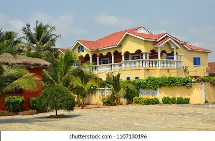 Beautiful photo of residential house in Africa with balconies and a red tile roof. Housing in Ghana. Wonderful urban landscape on a blue sky background Accra, Ghana - January 29, 2017