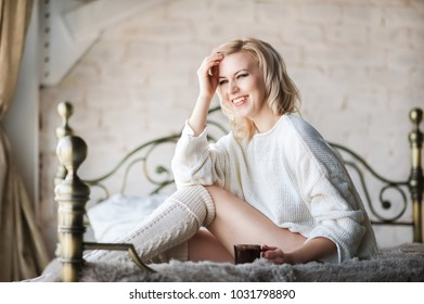 Beautiful photo of a sexy woman in the morning. Young girl in the morning in bed in a white sweater and with a cup of tea in hands. Blonde girl with short hair smiles. Unplugged mindfull.
