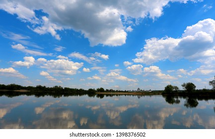 Beautiful photo of spring landscape with lake and sky. Reflections in the water.