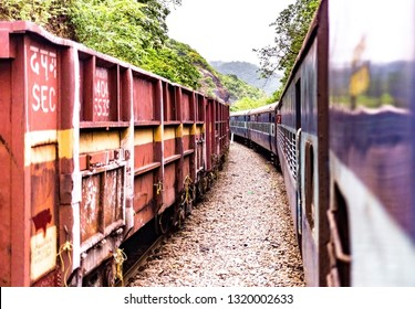 Beautiful Photo taken amidst greenery of Western Ghats while travelling a curve bend in Konkan Section of the Indian Railways. Goods train of SEC being halted at left is giving pass to Passenger train