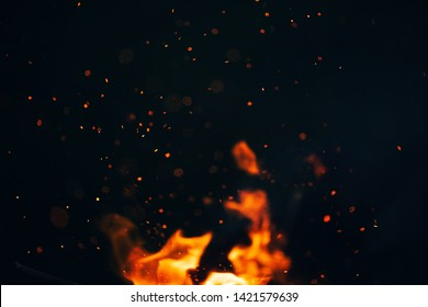 beautiful photo, the texture of the campfire at night, the flare of sparks in the air on a black background