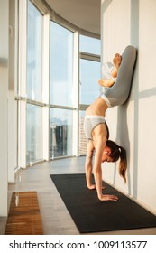 Beautiful photo of young woman in sporty top and leggings standing on her hands while practicing yoga on yoga mat at home with big windows isolated