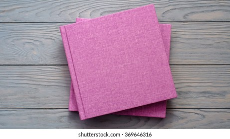 beautiful photobook in light pink textile cover on a grey wooden board, low depth of sharpness