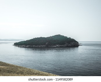 Beautiful photograph of the entire lush tree filled Island of Lokrum off the coast of Dubrovnik Croatia in the middle of the calm waters of the Adriatic Sea as seen from the walls surrounding Old Town