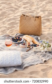 A beautiful picnic with fruit and wine at sunset near the sea