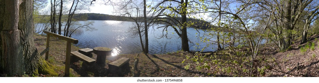 Beautiful picnic seat at the shore of a glacial lake in Mecklenburg-Western Pomerania near Sternberg (Panorama view) surrounded by a forest as a tourist attraction and for leasure time