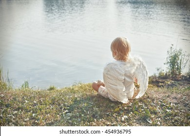 beautiful picture - angel valentine boy sitting on beach on sunset