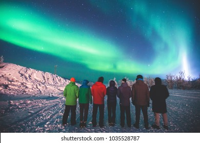 Beautiful picture of massive multicolored green vibrant Aurora Borealis, also known as Northern Lights in the night sky over winter Lapland landscape, Norway, Scandinavia, with a group of people