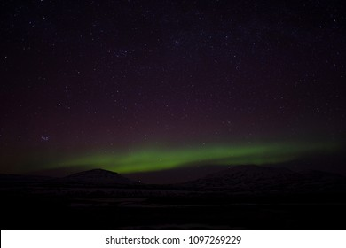 Beautiful picture of massive multicolored green vibrant Aurora Borealis, Aurora Polaris, also know as Northern Lights, in the night sky over Selfoss, Iceland.