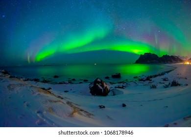 Beautiful picture of massive multicoloured vibrant Aurora Borealis, Aurora Polaris, also know as Northern Lights in the night blue sky over Lofoten Islands