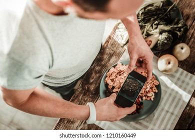 Beautiful picture. Nice smart man holding his smartphone while taking a photo of food