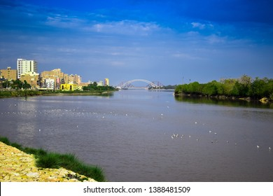 a beautiful picture of river indus river sukkur sindh pakistan and trees and buildings giving a look of urban city and bridges Ayub Bridge and Lansdowne Bridge .