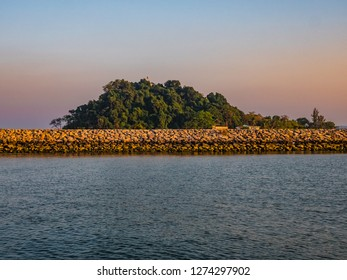Beautiful picture of a stone wall in the sea and a huge wooded area behind it in Thailand.