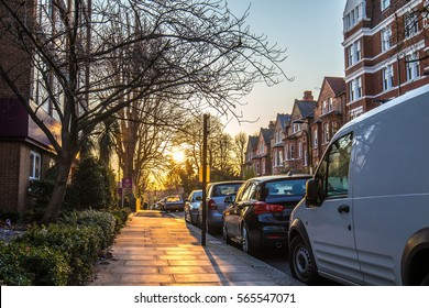Beautiful picture of the sunset in London suburbs, taken in the side walk with trees, cars and tipical flats showing
