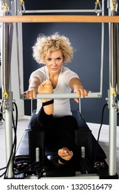 Beautiful Pilates instructor working on tower reformer