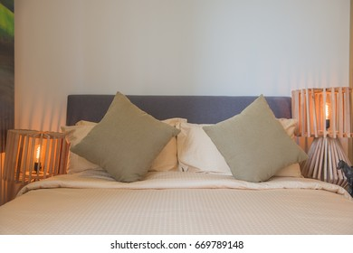 Beautiful  pillow on bed and light lamp on wall decoration in bedroom interior