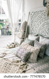 Beautiful pillows made by hands on the bed. Moroccan and Balinese style. White colors. Embroidered by hand