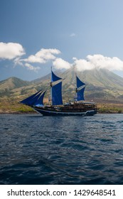 A beautiful Pinisi schooner sails by a remote volcano, Sangeang Api, just northwest of Komodo National Park, Indonesia. This area is known for its amazing marine biodiversity.