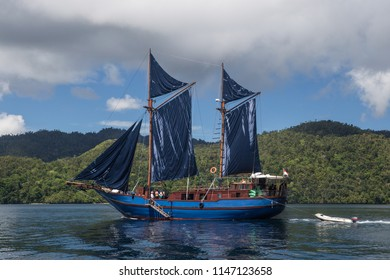 A beautiful Pinisi schooner sails in the calm waters of Raja Ampat, Indonesia. This remote, tropical region is known as the heart of the Coral Triangle due to its incredible marine biodiversity.