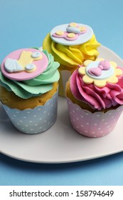 Beautiful pink, aqua blue and yellow cupcakes on white heart shape plate, for baby shower or children's party holiday and event.