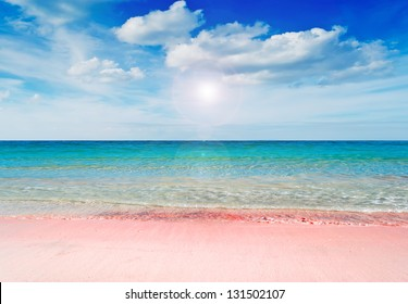 beautiful pink beach under a dramatic sky with sun reflection