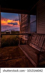 A beautiful pink and blue hued sunset, viewed from a time worn front porch with a swinging chair at an abandoned house in central Kentucky.