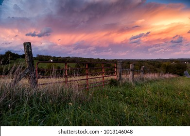 A beautiful pink and blue hued sunset on a partly cloudy evening, viewed through a worn farm gate in central Kentucky.