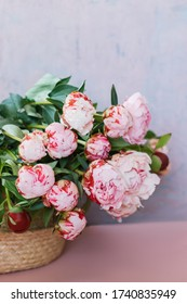Beautiful pink bouquet of peonies in a basket. Birthday background with copy space, vertical photo.