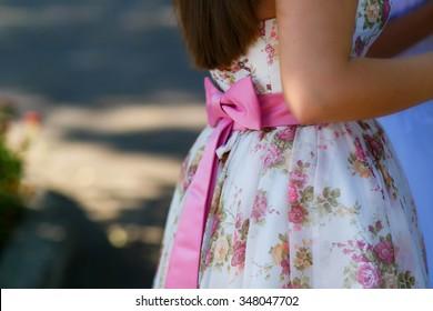 Beautiful pink bow on the little girl waist. Elegant beautiful flowered dress.
