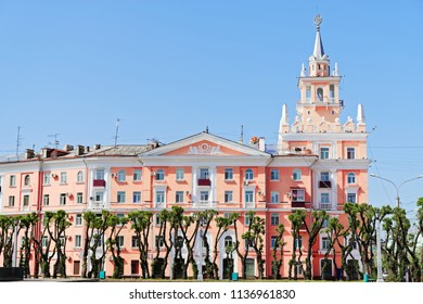 Beautiful pink building with spire against clear blue sky. This building is unofficial symbol of Komsomolsk-on-Amur