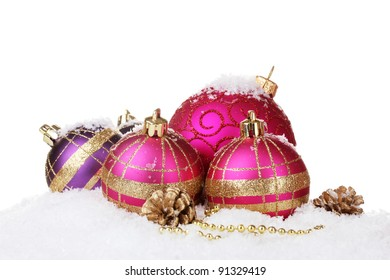 beautiful pink Christmas balls and cones on snow isolated on white