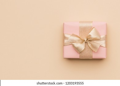 Beautiful pink christmas gift with golden ribbon isolated on beige paper background. Christmas present background with copy space.