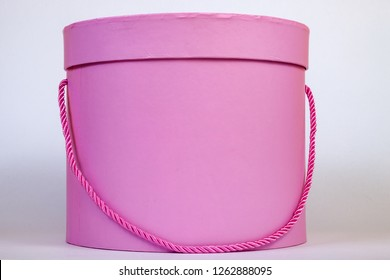 A beautiful pink circular gift box for packing a surprise inside with a closed lid and a cord instead of a ribbon close-up on a white background.