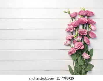 Beautiful pink eustoma flowers on white wooden background. Copy space, top view