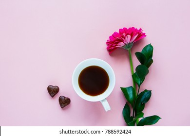 Beautiful pink gerbera flower, coffee cup and chocolate on pink background. Greeting card for Birthday, Woman or Mothers Day. Top view, flat lay