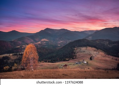 Beautiful pink and golden sunrise in autumn mountain landscape