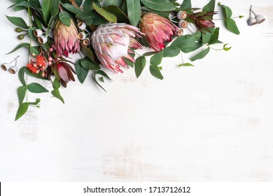 Beautiful pink king protea surrounded by  pink ice proteas, leucadendrons, eucalyptus leaves and flowering gum nuts, creating a floral border on a rustic white background.